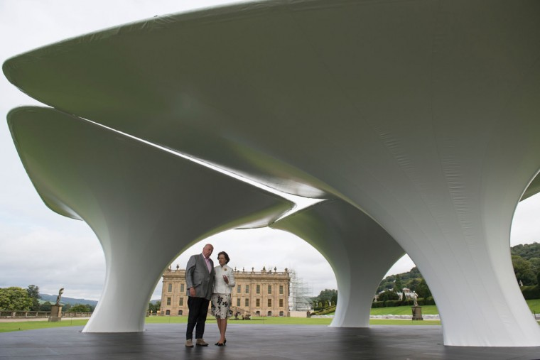 Peregrine 'Stoker' Cavendish (left), Duke of Devonshire, and his wife Amanda, Duchess of Devonshire pose for a photograph by Iraqi-born British architect Zaha Hadid entitled 'Lilas' that features in the 'Beyond Limits' exhibition in the grounds of Chatsworth House near Bakewell, northern England, on September 9, 2016. (OLI SCARFF/AFP/Getty Images)