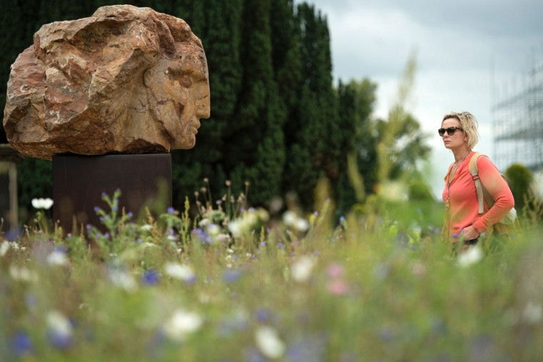 A woman studies a sculpture by British artist Emily Young entitled 'Red Mountain Head' that features in the 'Beyond Limits' exhibition in the grounds of Chatsworth House near Bakewell, northern England, on September 9, 2016. (OLI SCARFF/AFP/Getty Images)