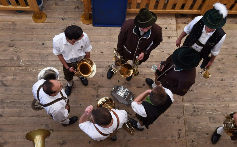 Brass musicians dressed in traditional costumes wait in a festival tent ahead the brass musician concert at the Theresienwiese Oktoberfest fair grounds in Munich, southern Germany, on September 25, 2016. The world's biggest beer festival Oktoberfest runs until October 3, 2016. (Christof Stache/AFP/Getty Images)