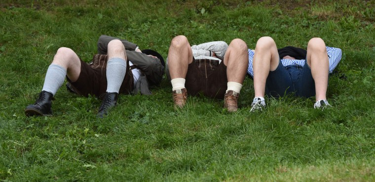 People lie in the grass at the Theresienwiese Oktoberfest fair grounds in Munich, southern Germany, on September 22, 2016. Oktoberfest, the world's biggest beer festival, runs until October 3, 2016. (Christof Stache/AFP/Getty Images)