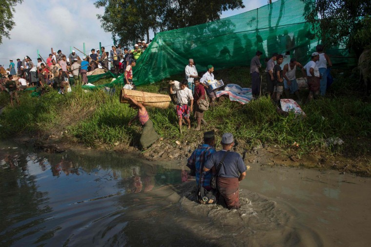 Members of Myanmar's Muslim minority arrive on a muddy field during a religious sacrifice of animals in observance of Eid al-Adha on September 13, 2016 in Thanlyin township instead of the town center, a move they said was because of complaints from some Buddhist residents. Muslims across the world are celebrating the annual festival of Eid al-Adha, or the festival of sacrifice, which marks the end of the Hajj pilgrimage to Mecca and commemorates prophet Abraham's readiness to sacrifice his son to show obedience to God. (Romeo Gacad/AFP/Getty Images)