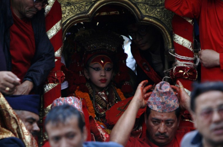 A Nepalese child revered as a living goddess, or Kumari, is carried during a procession held to honour the Kumari during the fourth day of the Indra Jatra festival in Kathmandu on September 16, 2016. Nepal's week-long festival celebrates 'Indra', the king of gods and the god of rains. Every September, the living goddess is carried on a palanquin in a religious procession through parts of the capital in a festival celebrated by Nepalese Hindus and Buddhists. / (AFP Photo/Prakash Mathema)