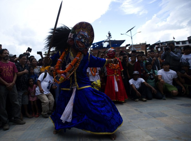 A Nepalese masked dancer performs the Sawa Bhaku dance during a chariot procession for the Kumari, revered in Nepal as a living goddess, during the fourth day of the Indra Jatra festival in Kathmandu on September 16, 2016. Nepal's week-long festival celebrates 'Indra', the king of gods and the god of rains. Every September, the living goddess is carried on a palanquin in a religious procession through parts of the capital in a festival celebrated by Nepalese Hindus and Buddhists. / (AFP Photo/Prakash Mathema)