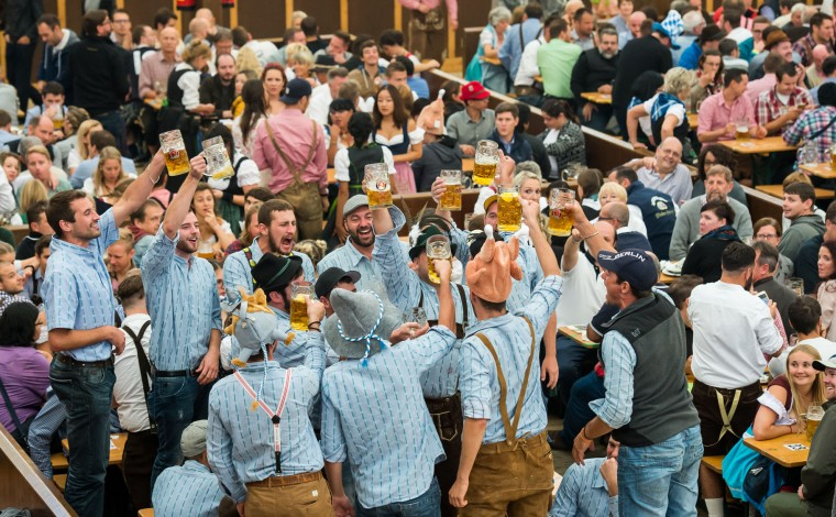 Visitors of the Paulaner beer tent hold up one-liter glasses of beer during day 2 of the 2016 Oktoberfest beer festival at Theresienwiese on September 18, 2016 in Munich, Germany. The 2016 Oktoberfest is taking place under heightened security due to fears over international terrorism. The fest will be open to the public through October 3. (Photo by Joerg Koch/Getty Images)