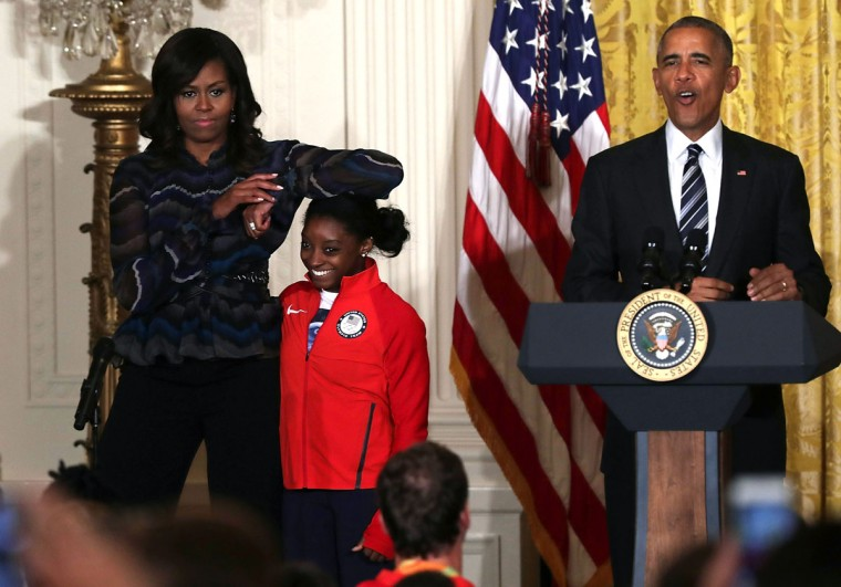 WASHINGTON, DC - SEPTEMBER 29: U.S. first lady Michelle Obama(L) rests her elbow on the head of Olympian Simone Biles (2nd L) as President Barack Obama (R) speaks during an East Room event at the White House September 29, 2016 in Washington, DC. President Obama and the first lady welcome the 2016 U.S. Olympic and Paralympic teams to the White House to honor their participation and success in the Rio Olympic Games this year. (Photo by Alex Wong/Getty Images)