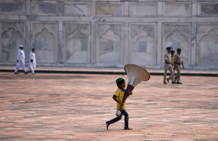 An Indian Muslim boy runs as he holds a speaker during the Eid al-Adha festival at the mosque inside the Taj Mahal in Agra on September 13, 2016. Muslims across the world celebrate the annual festival of Eid al-Adha, or the Festival of Sacrifice, which marks the end of the Hajj pilgrimage to Mecca and in commemoration of Prophet Abraham's readiness to sacrifice his son to show obedience to God. (Chandan Khanna/AFP/Getty Images)