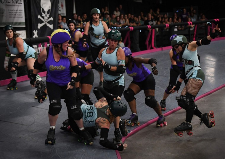 Members of the Varsity Brawlers team (purple tops) compete against the Tough Cookies team (Blue tops) during the L.A. Derby Dolls women's banked track roller derby event in Los Angeles, California on September 24, 2016. Roller Derby is a contact sport that originated in America and is based on two teams formation roller skating around an oval track, with points scored as one player known as a jammer laps members of the opposing team. The sport, which began in 1922, is played predominantly by women skaters with a strong emphasis on punk aesthetics, unique costumes and humorous stage names. (Mark Ralston/AFP/Getty Images)