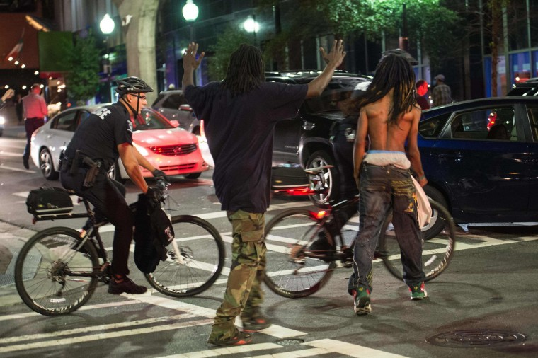 Protesters heckle policemen on bicycles during a demonstration against police brutality in Charlotte, North Carolina, on September 21, 2016, following the shooting of Keith Lamont Scott the previous day. Violence broke out in Charlotte, North Carolina for a second night as police braced for a repeat of confrontations ignited by the fatal police shooting of a black man. (Nicholas Kamm/AFP/Getty Images)