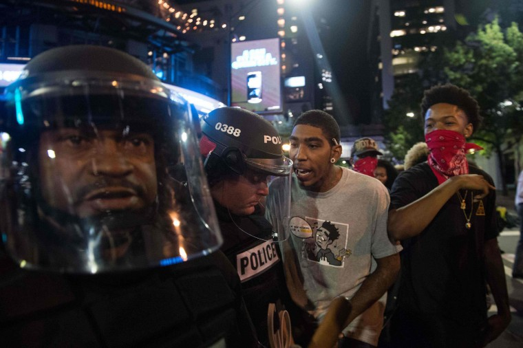 Protesters taunt riot police during a demonstration against police brutality in Charlotte, North Carolina, on September 21, 2016, following the shooting of Keith Lamont Scott the previous day. A protester in Charlotte, North Carolina was fatally shot by a civilian during a second night of unrest after the police killed a black man, officials said. (Nicholas Kamm/AFP/Getty Images)