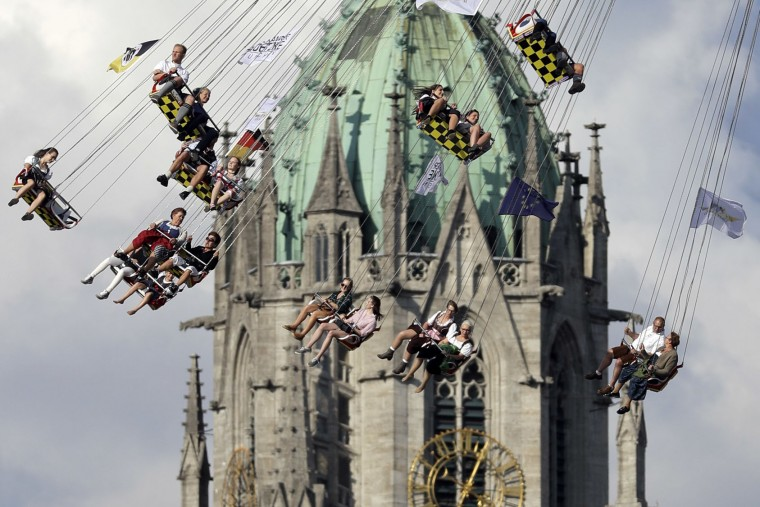 People ride a swing in front of the St. Paul's church at the 183rd Oktoberfest beer festival in Munich, Germany, Monday, Sept. 26, 2016. The world's largest beer festival will be held from Sept. 17 to Oct. 3, 2016. (AP Photo/Matthias Schrader)