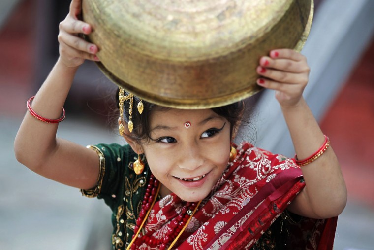 A young Nepalese girl wearing traditional attire plays with a vessel while waiting for the Kumari puja to start at Hanuman Dhoka temple, in Kathmandu, Nepal, Wednesday, Sept. 14, 2016. Girls under the age of nine gathered for the Kumari puja, a tradition of worshiping young prepubescent girls as manifestations of the divine female energy. The ritual holds a strong religious significance in the Newar community that seeks divine blessings to save small girls from diseases and bad luck in the years to come. (AP Photo/Niranjan Shrestha)