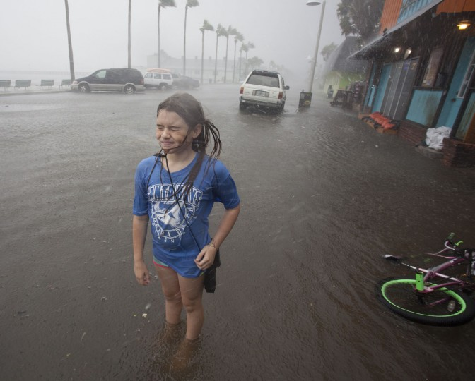 Hannah Coles, 9, takes a break from riding her bike to feel a strong rain band rain shortly Thursday afternoon, Sept. 1, 2016 in Gulfport, Fla. Coles was taking advantage of the day off from school to play in the rain and flooding. Tropical Storm Hermine strengthened into a hurricane Thursday and steamed toward Florida's Gulf Coast, (John Pendygraft/Tampa Bay Times via AP)