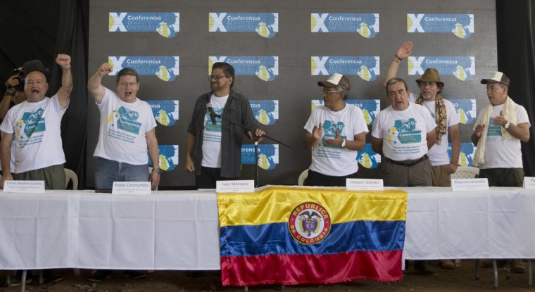 Leaders of the Revolutionary Armed Forces of Colombia, FARC, from left to right, Carlos Alonso Lozada, Pablo Catatumbo, Ivan Marquez, Joaquin Gomez, Mauricio Jaramillo,, Pastor Alape and Berturlfo Alvarez, celebrate after announcing that the rebel's 10th conference ratified a peace deal with the Colombian government, in Yari Plains, Colombia, Friday, Sept. 23, 2016. (AP Photo/Ricardo Mazalan)