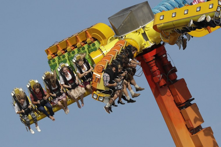People enjoy a fairground ride at the 183rd Oktoberfest beer festival in Munich, Germany, Monday, Sept. 26, 2016. The world's largest beer festival will be held from Sept. 17 to Oct. 3, 2016. (AP Photo/Matthias Schrader)