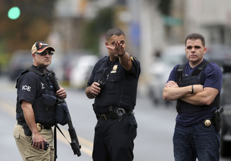 Police officers stand on Elizabeth Ave., in Linden, N.J., near where an Afghan immigrant wanted for questioning in the bombings that rocked a New York City neighborhood and a New Jersey shore town was taken into custody after being wounded in a shootout with police, authorities said, Monday, Sept. 19, 2016, in Linden. (AP Photo/Mel Evans)