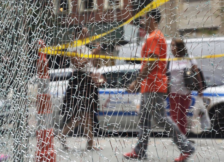 New Yorkers pass a shattered storefront window on W. 23rd St. in Manhattan, Tuesday, Sept. 20, 2016, in New York. The window was hit by shrapnel from the terrorist bomb that exploded across the street Saturday evening. An Afghan immigrant wanted in the bombings was captured Monday after being wounded in a gun battle with police. (AP Photo/Mark Lennihan)