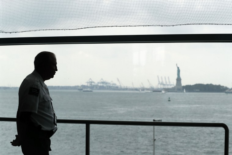 A private security guard stands at the Staten Island ferry terminal, with the Statue of Liberty in the background, Sunday, Sept. 18, 2016, in New York. Gov. Cuomo said 1,000 additional law enforcement officers were being deployed after the Saturday night blast in Chelsea, a primarily residential neighborhood on Manhattan's west side that's known for its art galleries and large gay population. He encouraged New Yorkers to go about their day as usual. (AP Photo/Mary Altaffer)