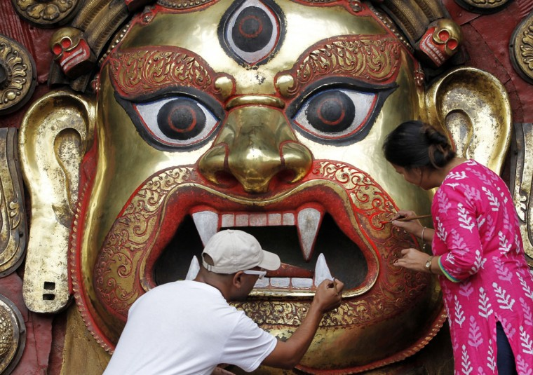Nepalese devotees paint a statue of Hindu god Swet Bhairav during the beginning of the week-long Indra Jatra festival at Basantapur Durbar Square in Kathmandu, Nepal, Tuesday, Sept. 13, 2016. Indra is considered the Hindu god of rain and the festival marks the end of the rainy season.(AP Photo/Niranjan Shrestha)