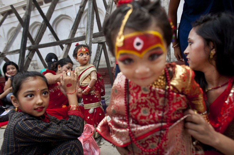 Young Nepalese girls wearing traditional costumes wait for the Kumari puja to start at Hanuman Dhoka temple, in Kathmandu, Nepal, Wednesday, Sept. 14, 2016. Girls under the age of nine gathered for the Kumari puja, a tradition of worshiping young prepubescent girls as manifestations of the divine female energy. The ritual holds a strong religious significance in the Newar community that seeks divine blessings to save small girls from diseases and bad luck in the years to come. (AP Photo/Niranjan Shrestha)