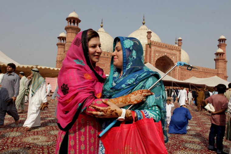 Pakistani Muslim women greet each other after offering Eid al Adha prayers at the Badshahi mosque in Lahore, Pakistan, Tuesday, Sept. 13, 2016. Pakistani Muslims are celebrating the Eid al-Adha, or the Feast of the Sacrifice, to mark the willingness of the Prophet Ibrahim -- Abraham to Christians and Jews -- to sacrifice his son. During the holiday Muslims slaughter sheep and cattle, distribute part of the meat to the poor. (AP Photo/K.M. Chaudary)