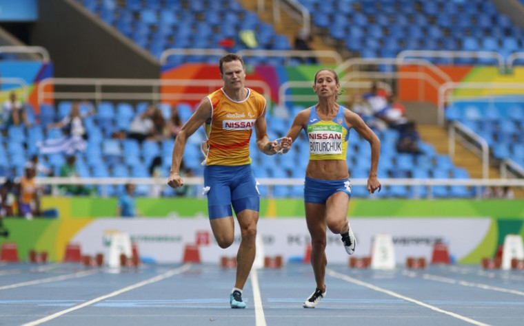 Oksana Boturchuk of Ukraine and her guide Volodymyr Burakov run in the women's 100M T12 first round, second heat at the 2016 Paralympic Games in Rio de Janeiro, Brazil, on Thursday. During the summer Paralympics, guides are used in cycling, equestrian, football-5-a-side, triathlon and track and field events. (David A. Barnes/University of Georgia via AP)