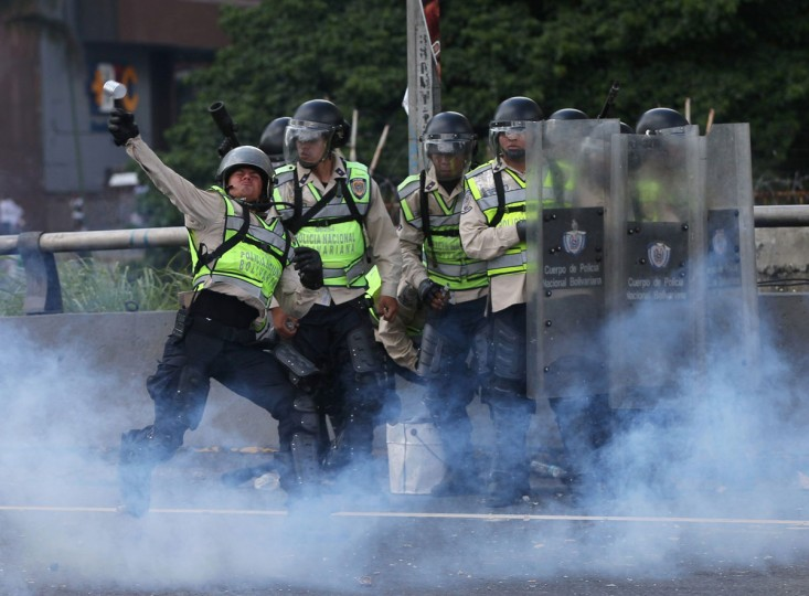 """In this Sept 1, 2016. photo, a Bolivarian police officer hurls a tear gas canister at demonstrators during a protest in Caracas, Venezuela. Venezuela's opposition is vowing to keep up pressure on President Nicolas Maduro after flooding the streets of Caracas with demonstrators Thursday in its biggest show of force in years. Protesters filled dozens of city blocks in what was dubbed the """"taking of Caracas"""" to pressure electoral authorities to allow a recall referendum against Maduro this year.(AP Photo/Fernando Llano)"""