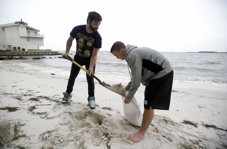 Daniel Fink, left, and Pete Stefani fill sandbags at the Cedar Cove Hotel as they prepare for Tropical Storm Hermine Thursday, Sept. 1, 2016, in Cedar Key, Fla. (AP Photo/John Raoux)