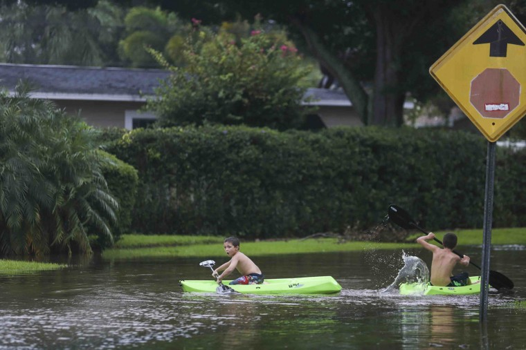 John Johnson, 8, left, and Joey Brooks, 12, play in their flooded neighborhood of Shore Acres in between passing thunderstorms during Tropical Storm Hermine in St. Petersburg, Fla., Thursday, Sept. 1, 2016. (Eve Edelheit/The Tampa Bay Times via AP)