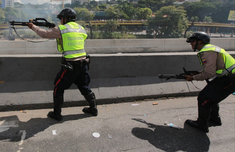 """Bolivarian National Police officers fire rubber bullets at demonstrators during an anti-government protest in Caracas, Venezuela, Thursday, Sept 1, 2016. Venezuela's opposition is vowing to keep up pressure on President Nicolas Maduro after flooding the streets of Caracas with demonstrators Thursday in its biggest show of force in years. Protesters filled dozens of city blocks in what was dubbed the """"taking of Caracas"""" to pressure electoral authorities to allow a recall referendum against Maduro this year.(AP Photo/Fernando Llano)"""