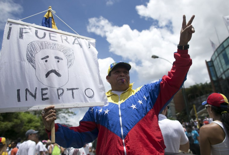 """A protester holds a sign with a drawing depicting Venezuela's President Nicolas Maduro and a message that reads in Spanish; """"Get out klutz"""" during a march in Caracas, Venezuela, Thursday, Sept. 1, 2016. Venezuela's opposition is vowing to keep up pressure on President Nicolas Maduro after flooding the streets of Caracas with demonstrators Thursday in its biggest show of force in years. Protesters filled dozens of city blocks in what was dubbed the """"taking of Caracas"""" to pressure electoral authorities to allow a recall referendum against Maduro this year. (AP Photo/Ariana Cubillos)"""