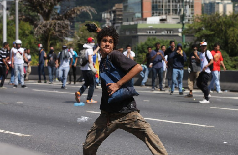 """An anti-government demonstrator winds up to throw a stone at police, during the """"taking of Caracas"""" march in Caracas, Venezuela, Thursday, Sept. 1, 2016. Venezuela's opposition is vowing to keep up pressure on President Nicolas Maduro after flooding the streets of Caracas with demonstrators Thursday in its biggest show of force in years. Protesters filled dozens of city blocks in what was dubbed the """"taking of Caracas"""" to pressure electoral authorities to allow a recall referendum against Maduro this year. (AP Photo/Fernando Llano)"""