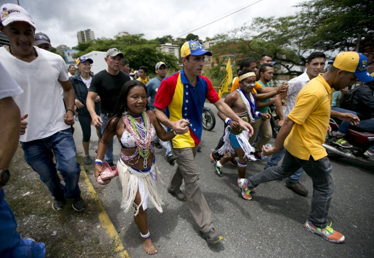 """Venezuela's opposition leader Henrique Capriles holds hands with a Piaroa Indian woman as they walk in the """"taking of Caracas"""" march in Caracas, Venezuela, Thursday, Sept. 1, 2016. Venezuela's opposition is vowing to keep up pressure on President Nicolas Maduro after flooding the streets of Caracas with demonstrators Thursday in its biggest show of force in years. Protesters filled dozens of city blocks in what was dubbed the """"taking of Caracas"""" to pressure electoral authorities to allow a recall referendum against Maduro this year. (AP Photo/Ariana Cubillos)"""