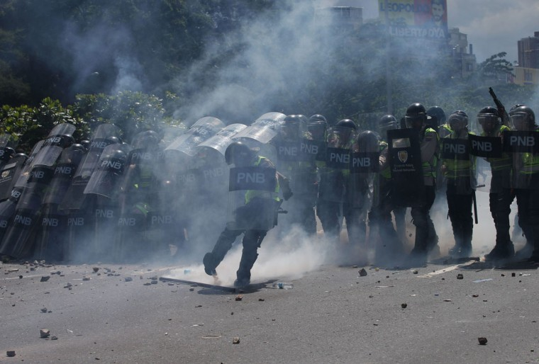 """Police officers aim tear gas at anti-government protesters in Caracas, Venezuela, Thursday, Sept. 1, 2016. Venezuela's opposition is vowing to keep up pressure on President Nicolas Maduro after flooding the streets of Caracas with demonstrators Thursday in its biggest show of force in years. Protesters filled dozens of city blocks in what was dubbed the """"taking of Caracas"""" to pressure electoral authorities to allow a recall referendum against Maduro this year. (AP Photo/Fernando Llano)"""