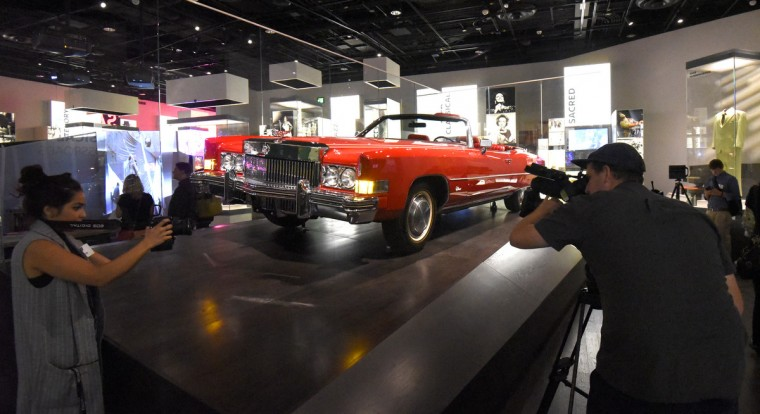 Members of the media photograph Chuck Berry's candy-apple red Cadillac at the National Museum of African American History and Culture. (Kim Hairston/Baltimore Sun)