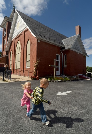 Branson Taylor, 4, with his sister Paislee, 2, run outside the West Liberty United Methodist Church, as they leave the daycare center at the church. The area once called Trump is now known as West Liberty, a neighborhood within the unincorporated community of White Hall in northern Baltimore County. (Amy Davis/Baltimore Sun)