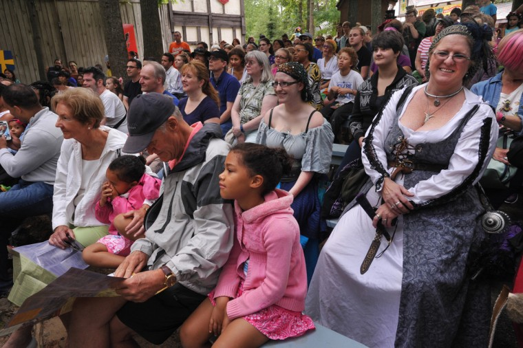 The audience for The Royal Welcome show includes Nyla Hendrick, of Annapolis, right, and her daughter, Aurora Hendrick, seated to her right. Like many visitors to the Maryland Renaissance Festival, both are dressed in period costume. In front center is Paige Jordan, of Crofton, MD, who came with her sister Grace and grandparents, Diana and Philip DeVries of Roxbury, CT.  (Amy Davis/Baltimore Sun)