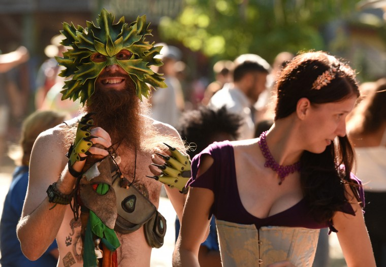 "Danny ""Rat"" Ventsias, a regular at the Maryland Renaissance Festival, wears a foliage mask and other accessories to play The Green Man, celebrating nature. At right is Renee Thompson of Towson.   (Amy Davis/Baltimore Sun)"