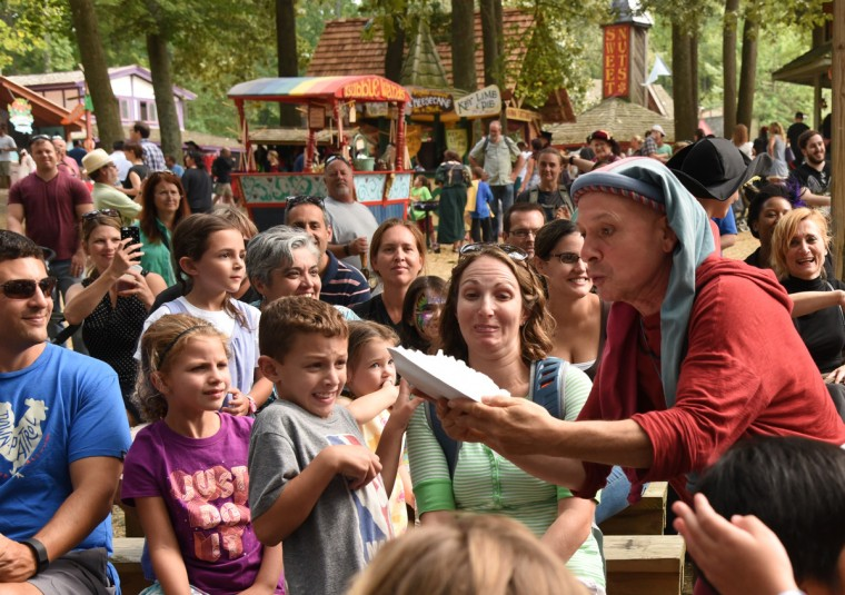 "Mark Jaster, the silent half of ""A Fool Act Named ""O"" and ""LaLa,""  leaps from the stage into the audience with a pie at the Renaissance Festival.  (Amy Davis/Baltimore Sun)"