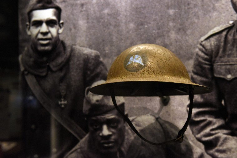 U.S. infantry helmet worn by African American troops in WWI.  In background is a photo of soldiers of the 369th Regiment, nicknamed the Harlem Hellfighters.  The 369th received the Croix de Guerre, a French military award from bravery in battle.    (Kim Hairston/Baltimore Sun) 48406.