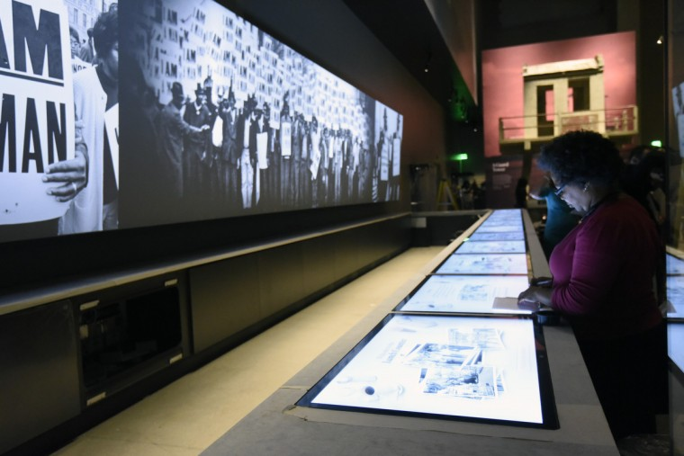 Visitors examine an interactive lunch counter display about the sit-ins and civil rights protests in North Carolina. (Kim Hairston/Baltimore Sun) 34582.