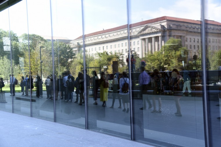 Visitors are reflected the glass of the Smithsonian National Museum of African American History and Culture (NMAAHC) as members of the media line up for a preview. (Kim Hairston/Baltimore Sun) 7445.