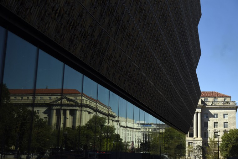 An image of the William Jefferson Clinton Federal Building reflects on the Smithsonian's National Museum of African American History and Culture (NMAAHC).  (Kim Hairston/Baltimore Sun)