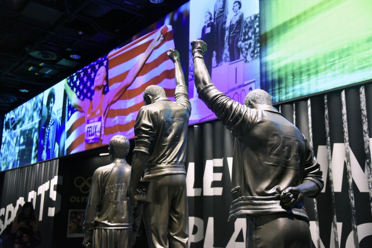 Sculpture of, center, #307 Tommie Smith and, right,  #259 John Carlos October 16, 1968 at the Olympics in Mexico City. The athletes raised gloved fists on the podium during the National Anthem to protest racial discrimination in the United States.  (Kim Hairston/Baltimore Sun)