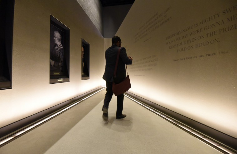 A man walks past a portrait of Susan B. Anthony at  the National Museum of African American History and Culture. (Kim Hairston/Baltimore Sun)