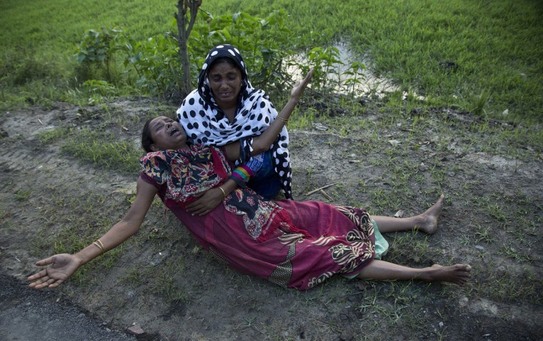 Mazida Beghum, 40, mother of Anjuma Beghum, 18, who was killed in police firing wails at Bandardubi village on the periphery of the Kaziranga National Park, northeastern Assam state, India, Monday, Sept. 19, 2016. Authorities ordered the demolition of around 300 houses in three villages to evict people living on the periphery of the rhino sanctuary to stop rampant poaching of the rare animal, a top police official said. Two people were killed and several others were injured Monday when villagers clashed with police while protesting the demolition of their homes. (AP Photo/Anupam Nath)