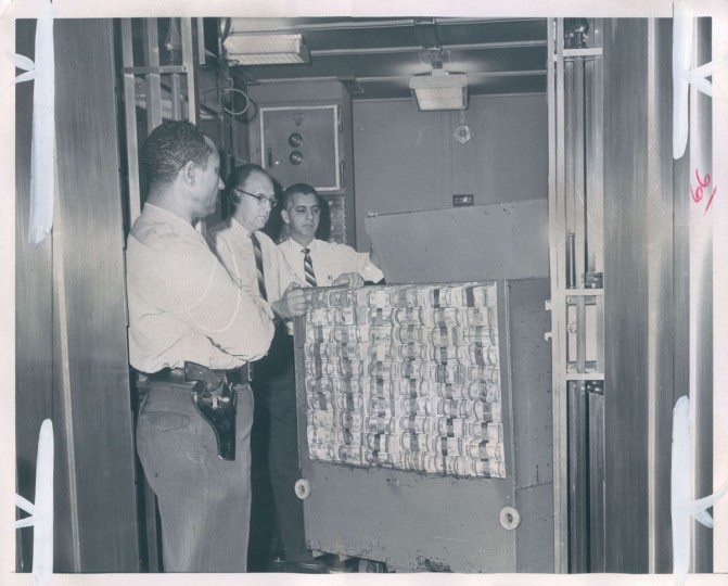 """There's $3,000,000 here,"" read the caption to this 1967 photo. ""This is only a part of the bundles of bills which daily move into and out of the Federal Reserve Bank branch as it supplies Maryland banks with the necessary cash to conduct business. Left to right--Julius H. Pryor, a guard; Edward Gluth and S.J. Sinnicchio."" (Gardina/Baltimore Sun)"