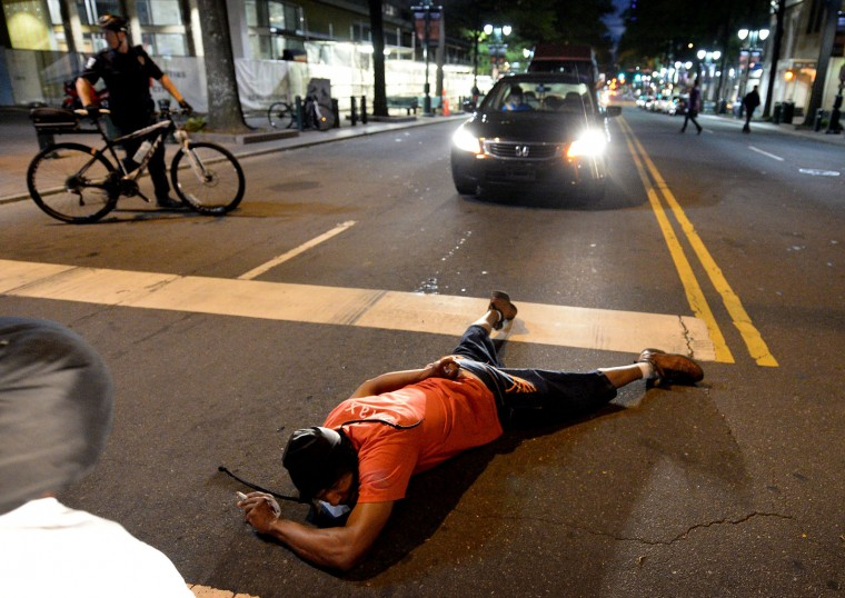 A protestor blocks an intersection at Trade and Tryon Streets in Charlotte, N.C., on Wednesday, Sept. 21, 2016. The protestors were rallying against the fatal shooting of Keith Lamont Scott by police on Tuesday evening in the University City area. (Jeff Siner/The Charlotte Observer/TNS)