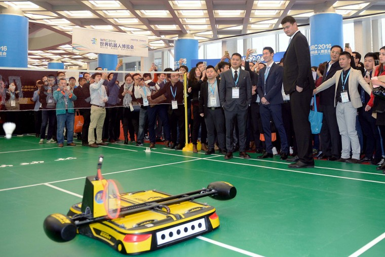 This photo taken on October 20, 2016 shows former Chinese basketball star Yao Ming watching a robot playing badminton during the 2016 World Robot Conference in Beijing. More than 2,000 contestants from different countries and regions take part in the conference on October 20 to 25. (STR/AFP/Getty Images)
