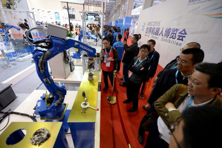 This photo taken on October 20, 2016 shows visitors watching a robot from YASKAWA welding during the 2016 World Robot Conference in Beijing. More than 2,000 contestants from different countries and regions take part in the conference on October 20 to 25. (STR/AFP/Getty Images)