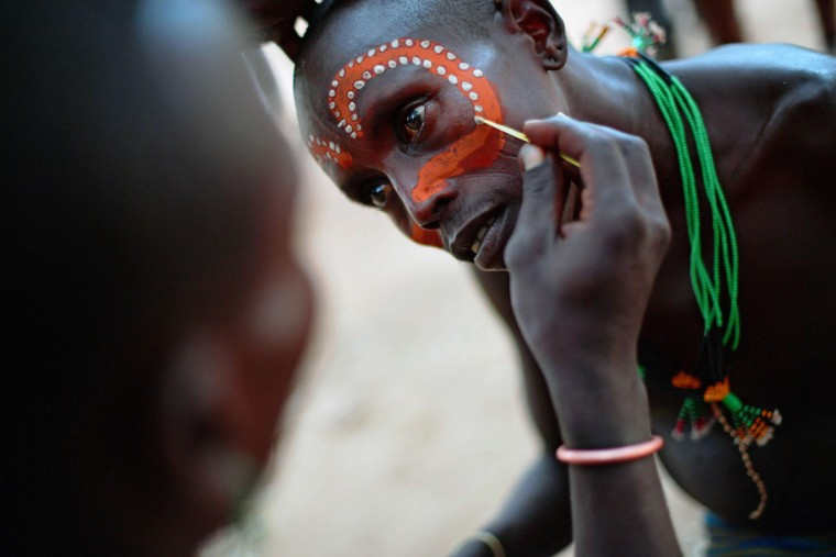 """A Hamar man has his face painted before a bull jumping ceremony in Ethiopia's southern Omo Valley region near Turmi on September 19, 2016. The Hamar are a Nilotic ethnic group in Ethiopia. Bull jumping has been practised by the Hamars for thousands of years. The ceremony is a coming of age tradition which allows young men to marry. The man has to run across the backs of bulls which have been lined up, 4 times. If he falls through the row of bulls he is to start again until he finishes without falling. If the man fails to properly """"jump the bulls"""" he risks humiliation and being cast out by his village as well as never being able to marry in the future. Before the ceremony women line up to be whipped by men holding sticks to prove their devotion to the men. The construction of the Gibe III dam, the third largest hydroelectric plant in Africa, and large areas of very """"thirsty"""" cotton and sugar plantations and factories along the Omo river are impacting heavily on the lives of tribes living in the Omo Valley who depend on the river for their survival and way of life. Human rights groups fear for the future of the tribes if they are forced to scatter, give up traditional ways through loss of land or ability to keep cattle as globalisation and development increases. (AFP PHOTO / CARL DE SOUZA)"""